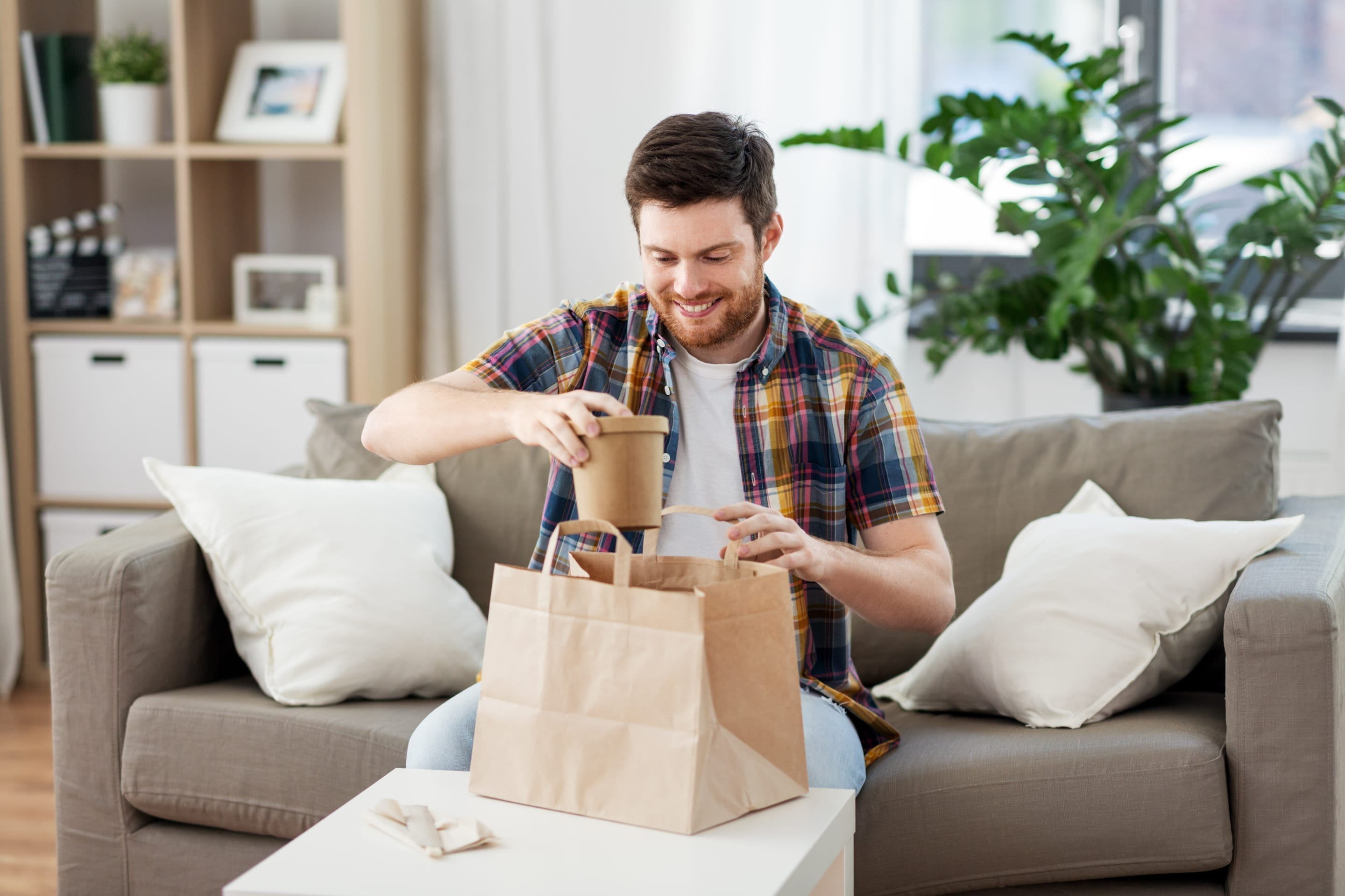 Smiling man eating takeout food.